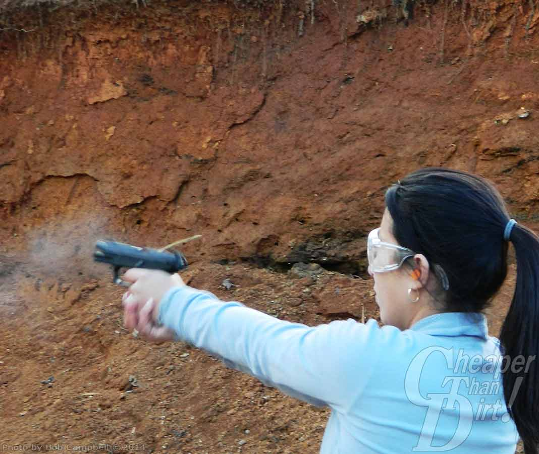 Young woman in light blue shirt, black hair and eye protection shoots a Walther P22 against a light brown dirt background.