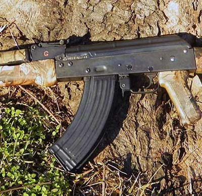 AK-47 with camo finish lying on a against a tree, barrel pointed down and to the right.