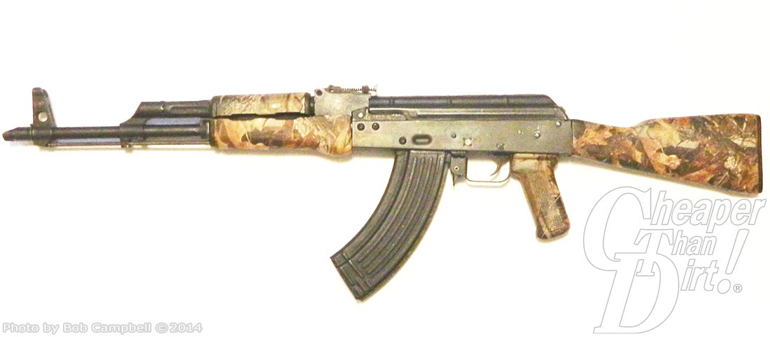 Camo AK-47 pointed to the left on a white background.