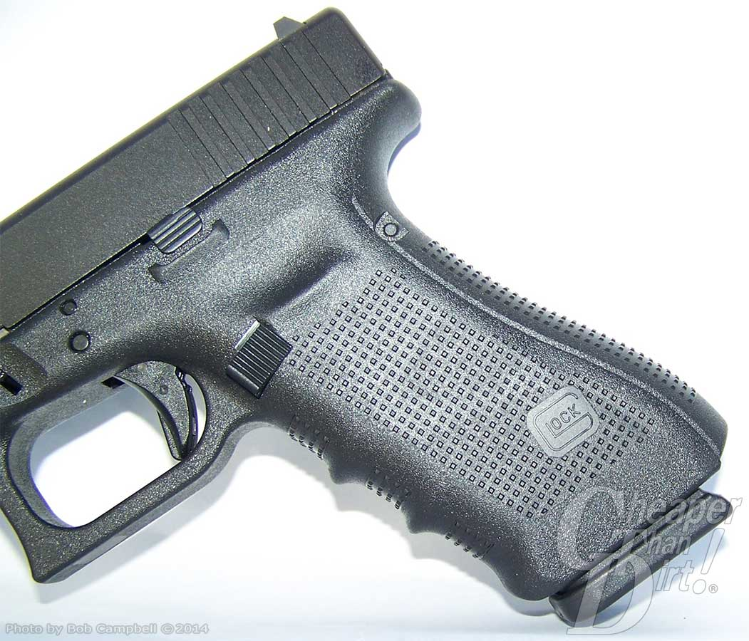 Dark gray Glock 17 Gen 4 with focus on textured frame and the extended magazine release button. Barrel is pointed down and to the left on a white background, with a gray strip at the bottom.