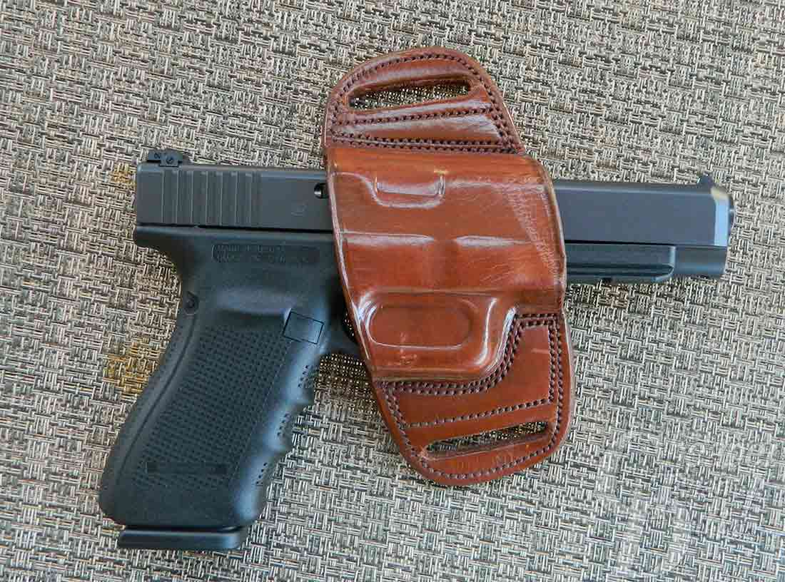 Medium brown Tagua belt slide with dark gray Glock 41, barrel pointed to the right on a woven gray-and-white background.