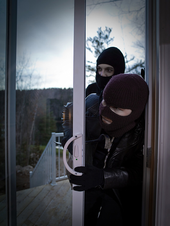 Two people with dark ski masks breaking into a home through the sliding glass door.