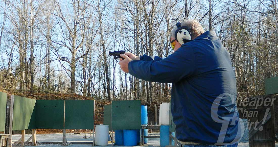 White-haired man in blue jacket with white ear protection points the Ruger LCR at a green target set against a backdrop of leafless trees.