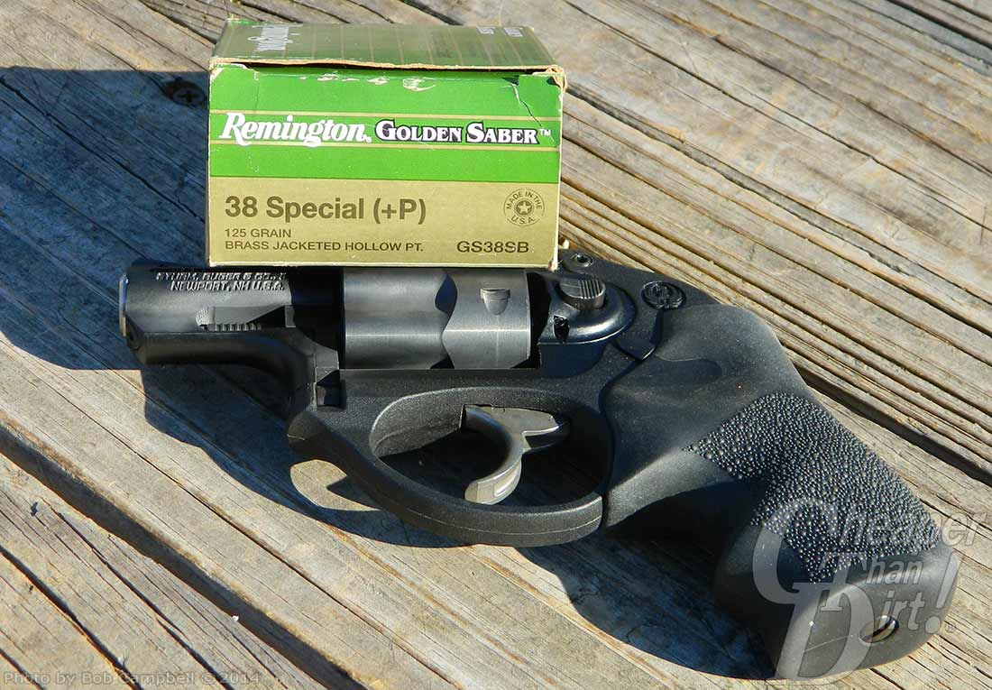 Light and bright green box of Remington Golden Saber ammunition on top of a charcoal colored Ruger LCR on worn wooden planks.