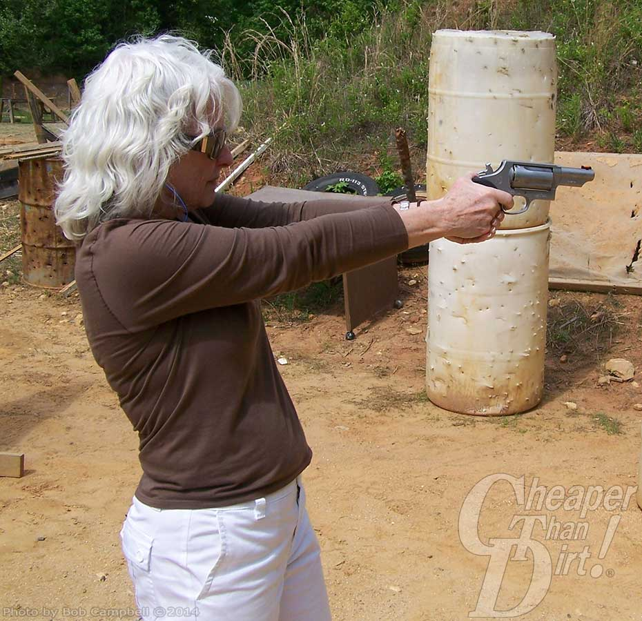 White haired woman in light brown shirt with sunless points a silver Taurus Judge straight in front of her for target practice against a background of miscellaneous items and greenery.