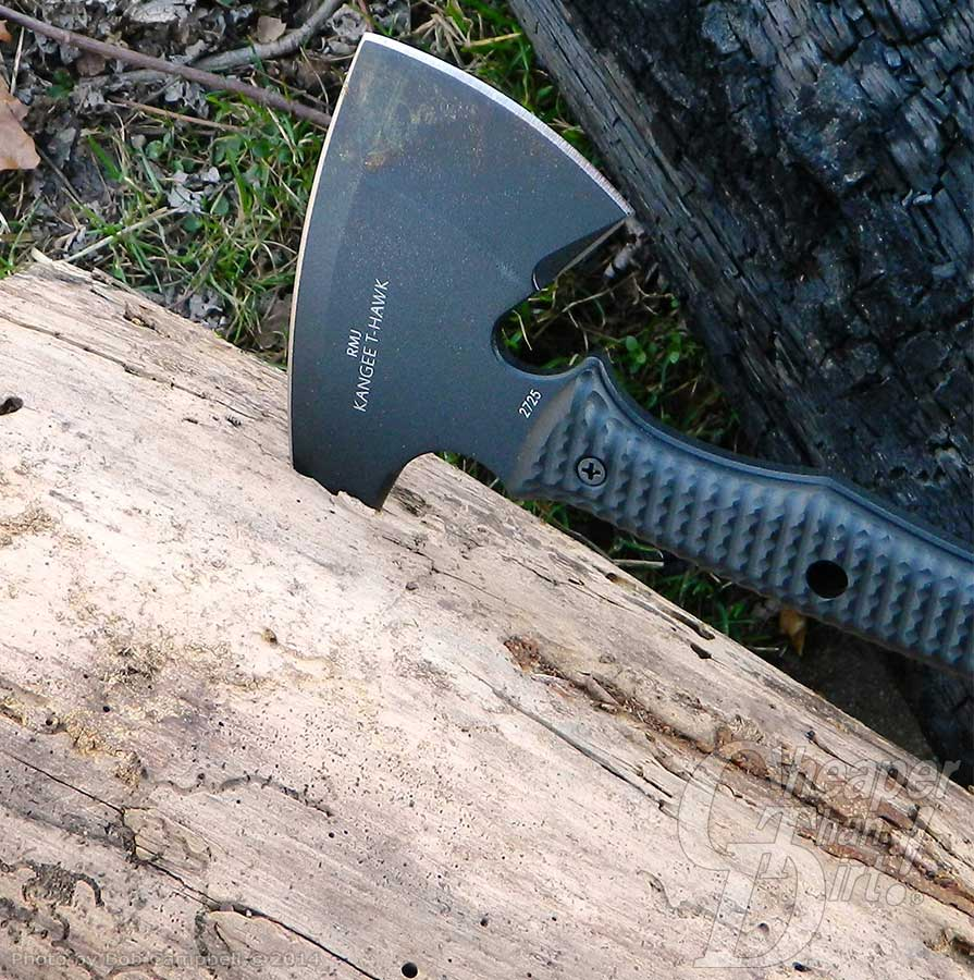 Black CRKT T-Hawk with the other end in a tree trunk.