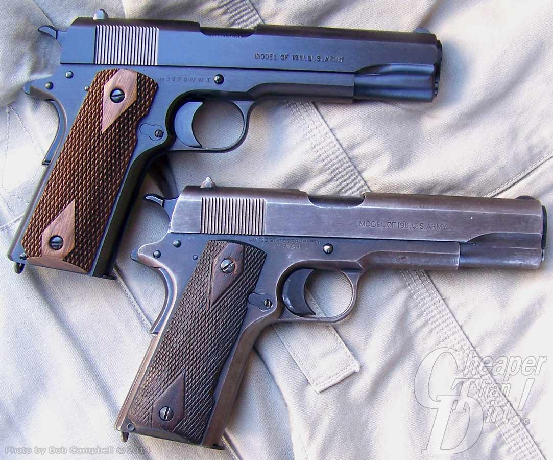 New black Colt pistol with brown grip on top, barrel pointed to the right. 97-year-old pistol with worn grips on the bottom.Both lying on a white shirt.