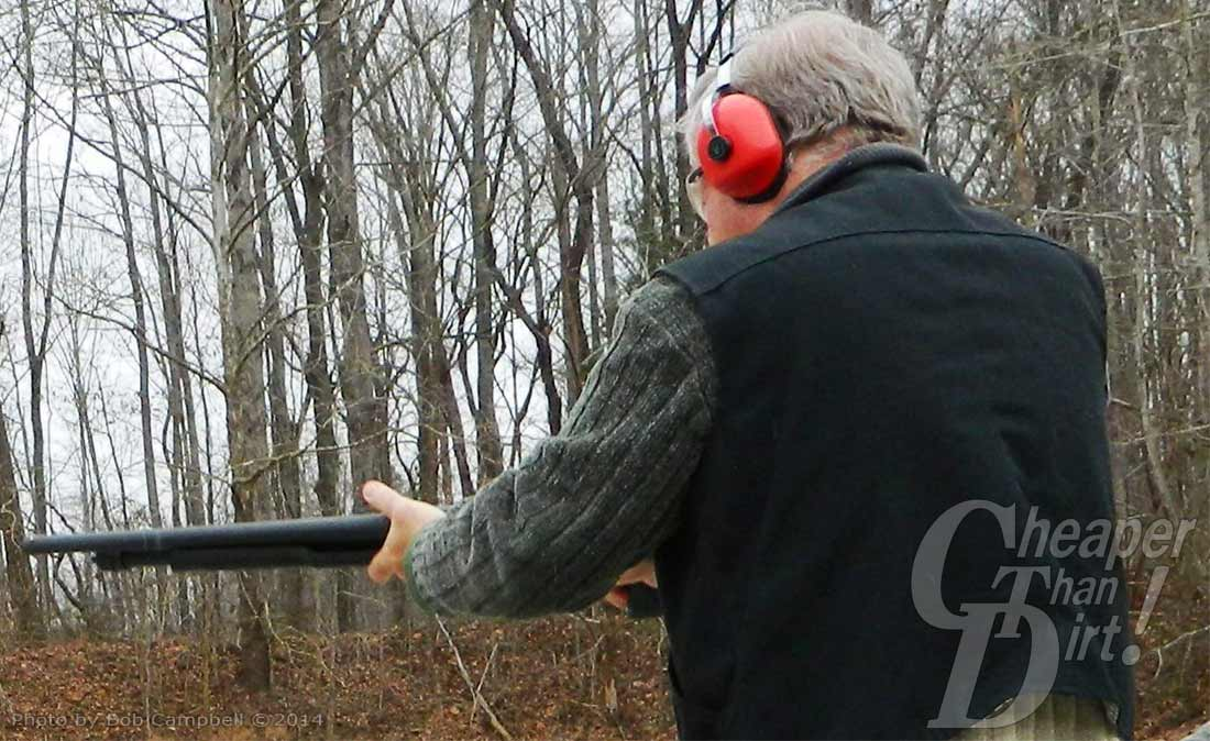 Gray haired man with a black vest and red ear protection shoots the Stevens 320 into a wooded area.