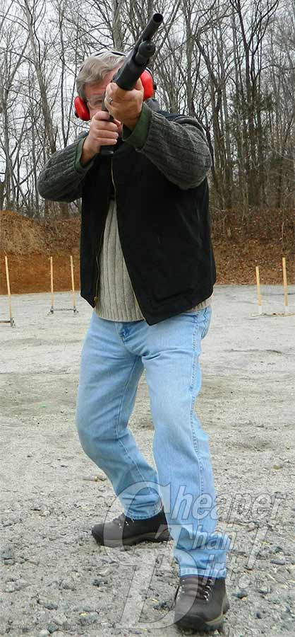 Gray haired man with a black vest and red ear protection shoots the Stevens 320 shooting in the air with a wooded area behind him and concrete beneath his feet.