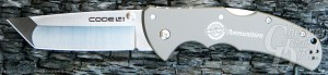 Silver Cold Steel Code 4 knife with blade open on a gray stone background.