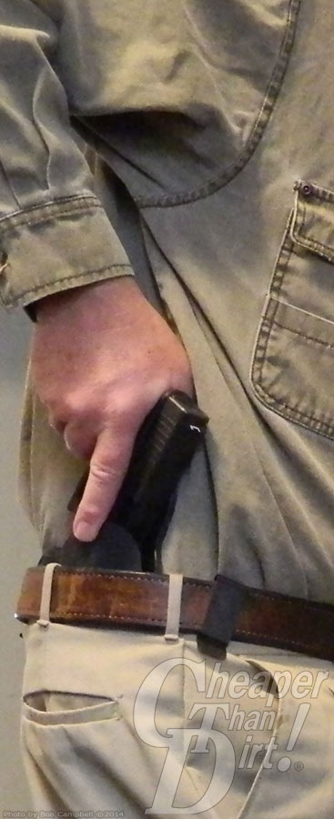 Man in tan shirt and pants with his hand holding onto a gun in his waistband.
