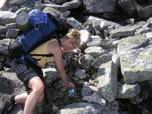 Picture shows a hiker filling up a water bottle from a small stream on some rocks.