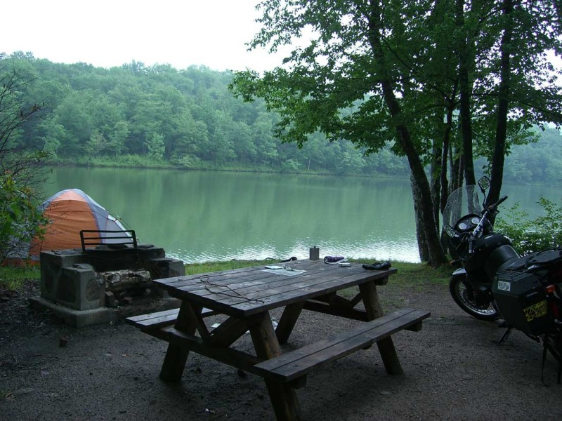 Picture shows a pitched tent and picnic table by the lake.