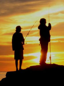 Two men holding fishing poles against an orange sunset.