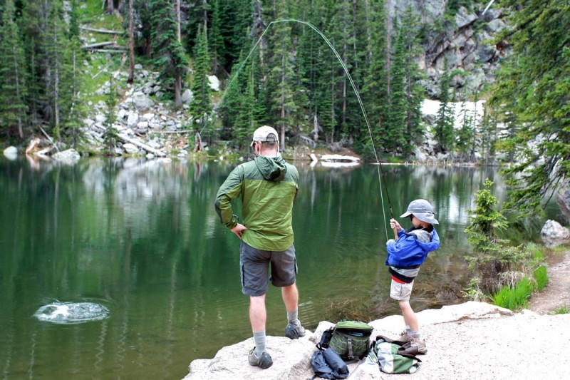 Man and his young son pulling in a fish from a lake.