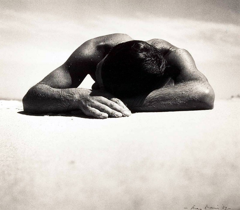 Picture shows a topless man laying face down, dripping with sweat in a hot, dry desert.