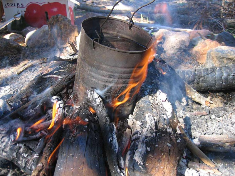 Picture shows a tin can sitting on a small, open campfire.