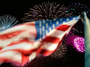 Night sky lit up with fireworks and an American flag flying in the foreground.