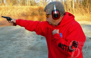 A gray-haired man in a bright red sweatshirt with black/red ear protection shoots a Smith and Wesson M13 .357 Magnum at a target with a brown wooded area behind him.
