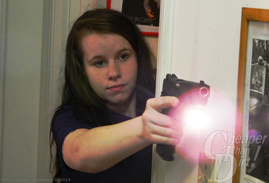 A dark haired young woman in a black t-shirt shoots a 1911 with a rail light