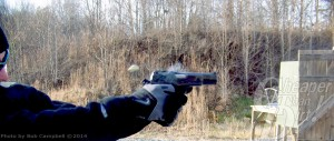 Man in navy blue sweater and gloves firing a mm at a target with a wooded area in the background.