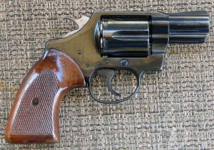 A Colt Detective Special with a brown grip, barrel pointed to the right on a gray-and-white woven background.