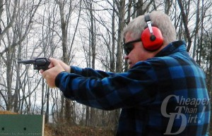 A gray-haired man in a blue and black plaid jacket with red ear protection fires a Smith and Wesson Miliary and Police .38 at a target with a wooded area behind him.