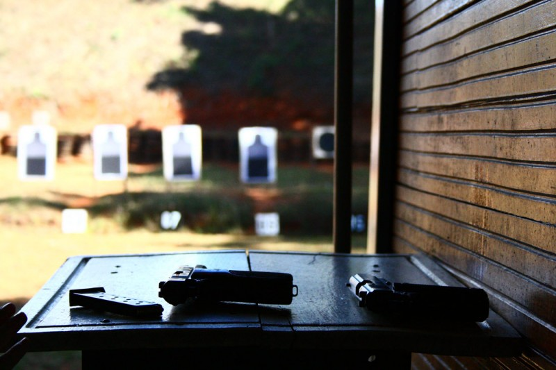 Picture shows the inside of an outside shooting range looking down range at black and white targets.