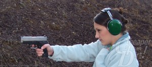 A young woman in a light blue shirt with ear protection shoots the SIG P229 at a target.