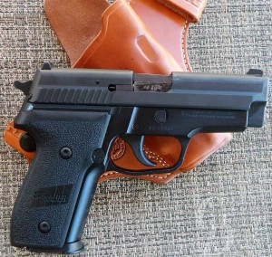 A black SIG P229 lying on a holster.
