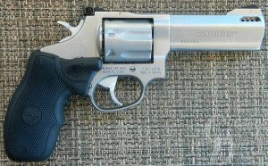 Silver barreled-Taurus Track 637SS, barrel pointed to the right on a gray-and-white woven background.