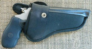 Black leather holster with the black grip showing, barrel pointed to the right.