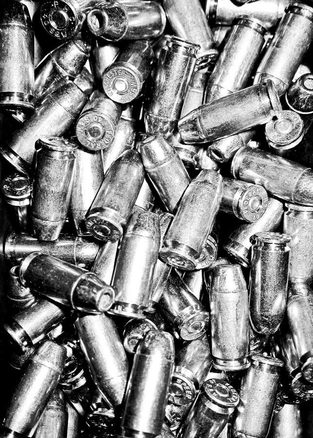 Picture shows a pile of ammunition in black and white.