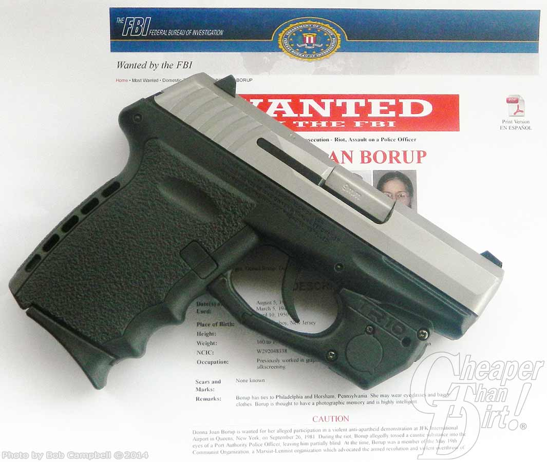 A 9mm with black handle and silver rail, lying on a Wanted poster.