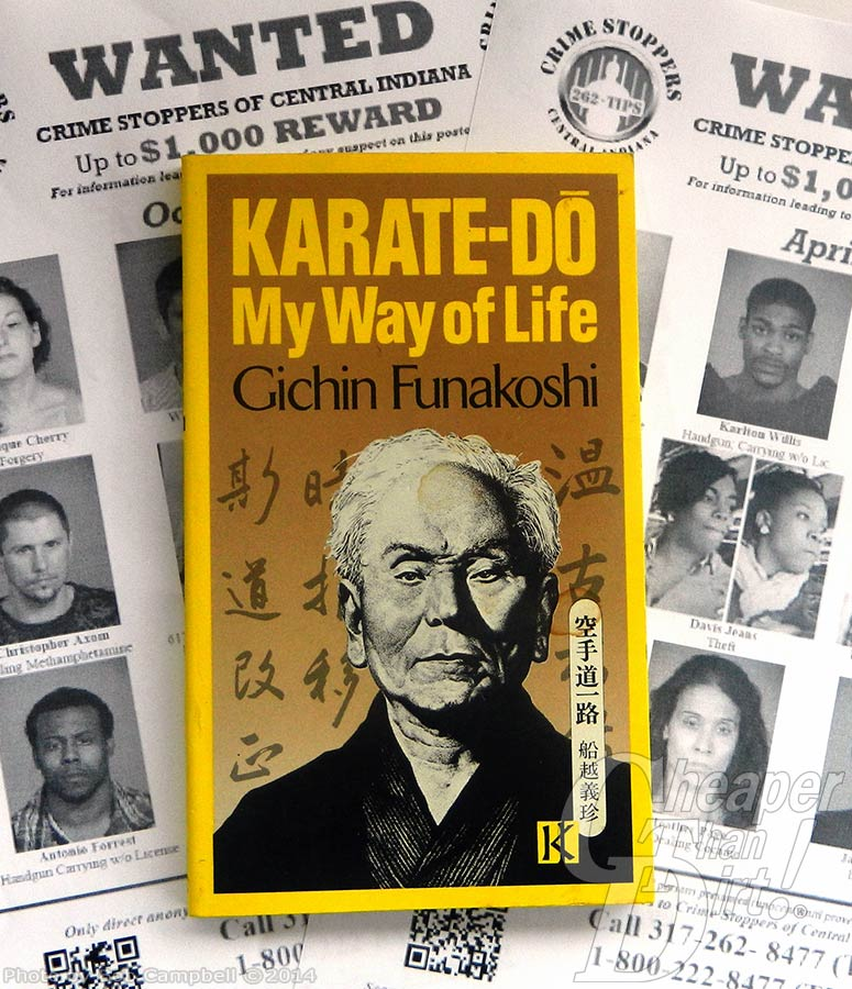 Picture of wanted posters in the background with the book cover of Karate-Do: My Way of Life in the foreground