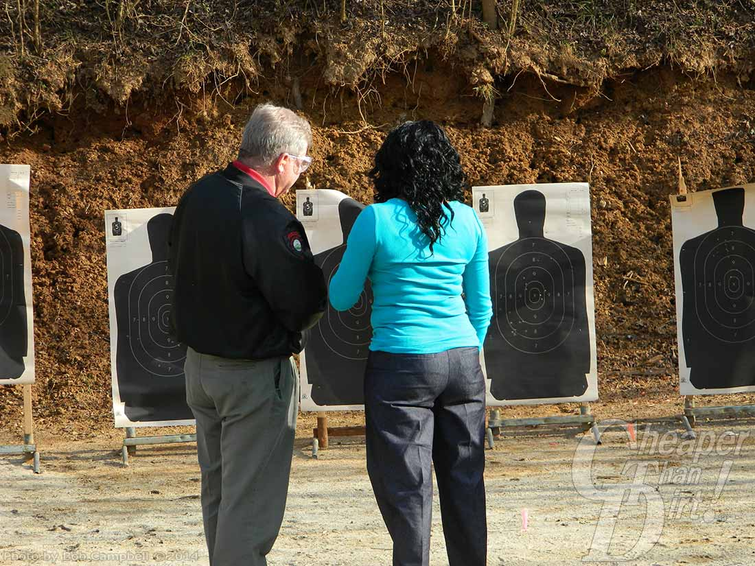 A gray haired man in a black jacket shows a dark-haired woman in teal shirt and jeans how to hit the target.