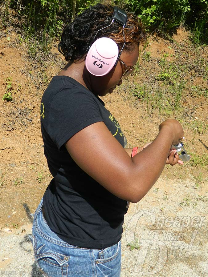 Young woman in black t-shirt and jeans with pink ear protection practices loading her firearm, with a wooded area in the background.