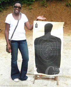 A young woman in a white t-shirt and jeans stands next to her practice target
