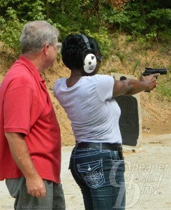 An instructor in a red shirt stands behind a student in a white shirt and dark jeans, firing at a target.