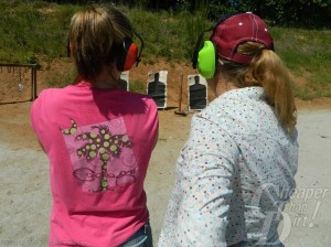 Two young women, one in a pink t-shirt, one in a white shirt, face a shooting range