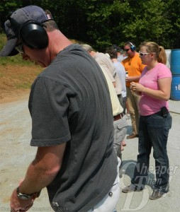 A man in a gray t-shirt with ear protection is under the watchful eye of a range officer who is keeping the shooters safe.