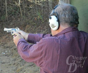 Gray haired man in purple shirt with ear protection shoots his handgun into the woods.