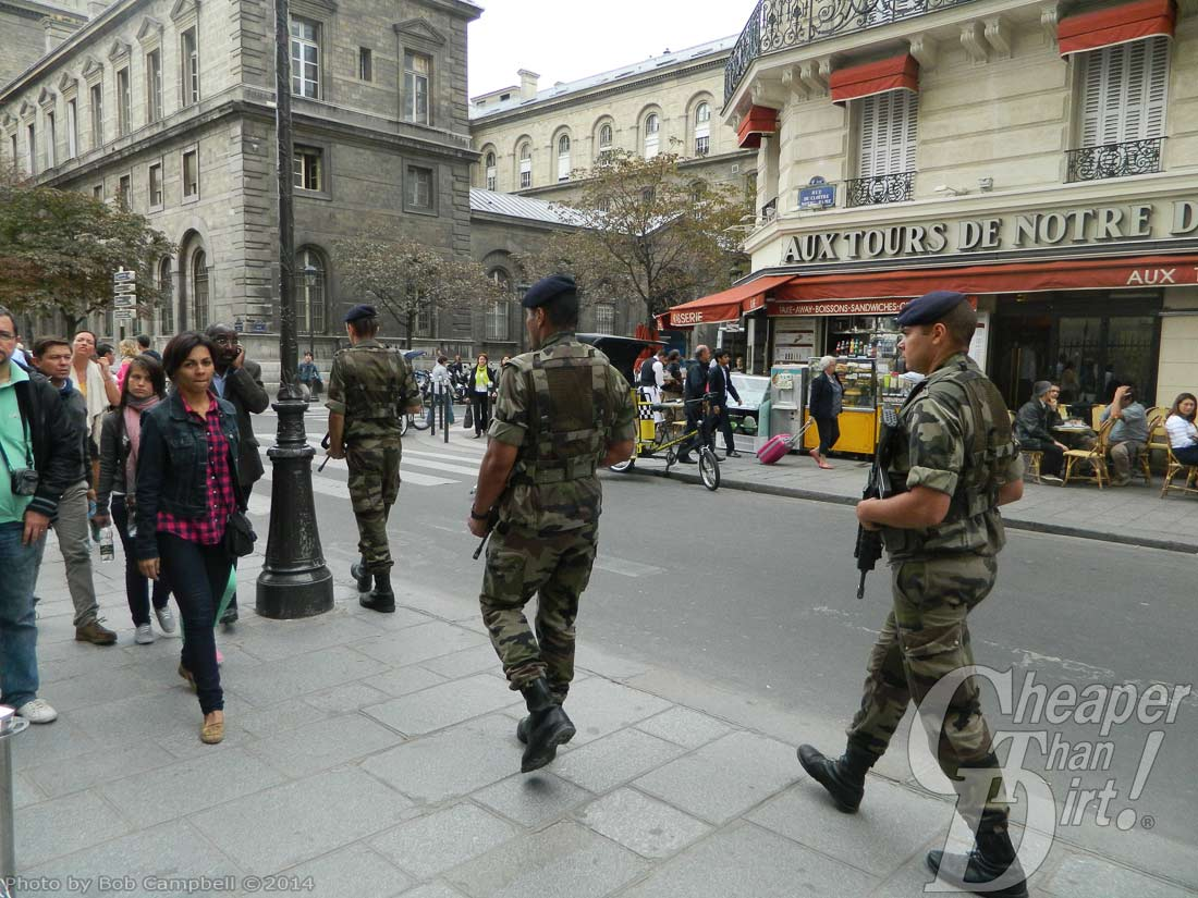 2 paratroopers walk along a busy street with guns pointed down, yet ready
