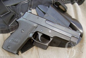 Dark gray SIG P220 .45, barrel pointed down and to the right on a light tan background