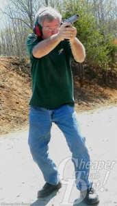 White haired man in green shirt and bluejeans fires his gun to master the piece, with wooded area behind him.