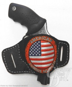 Black handled Taurus 605 in a black holster with American flag, barrel pointed down on a white-to-gray background