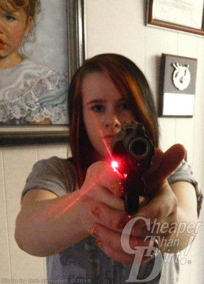 Young lady pointing a handgun with a Crimson Trace lasergrip toward you the viewer