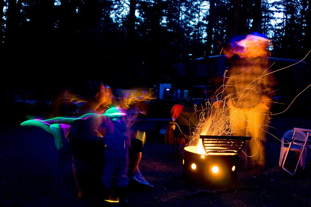 Picture shows campers playing with glow sticks around a campfire at night.