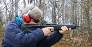 Gray-haired man in blue jacket with red ear protection shoots a pistol carbine into the woods.