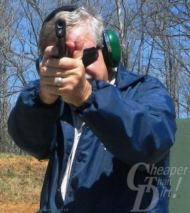 Man in dark navy jacket, gray hair and green hearing protection shooting an RIA Tactical II at the range, barrel pointed toward you as the viewer
